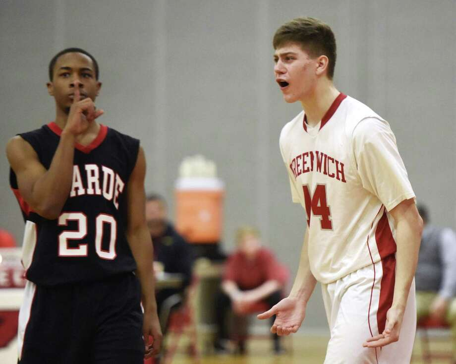 Greenwich's Robert Clark (14) questions the official's call at the end of the game as Fairfield Warde's Rashad Butler (20) silences the crowd as time expires. Photo: Tyler Sizemore / Hearst Connecticut Media / Greenwich Time