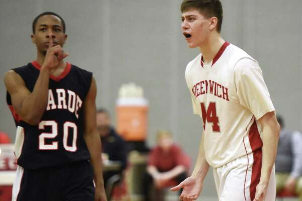 Greenwich's Robert Clark (14) questions the official's call at the end of the game as Fairfield Warde's Rashad Butler (20) silences the crowd as time expires.