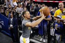 Stephen Curry (30) attempts his signature tunnel shot as fans gather by the dozens over the team entrance at Oracle Arena in Oakland, Calif., on Friday, October 21, 2016.