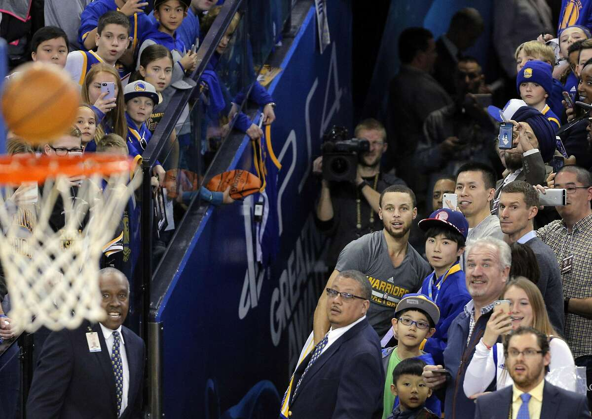 Stephen Curry (30), guards and fans watch a ball almost go in as Curry attempts his signature tunnel shot as fans gather by the dozens over the team entrance at Oracle Arena in Oakland, Calif., on Wednesday, February 1, 2017.