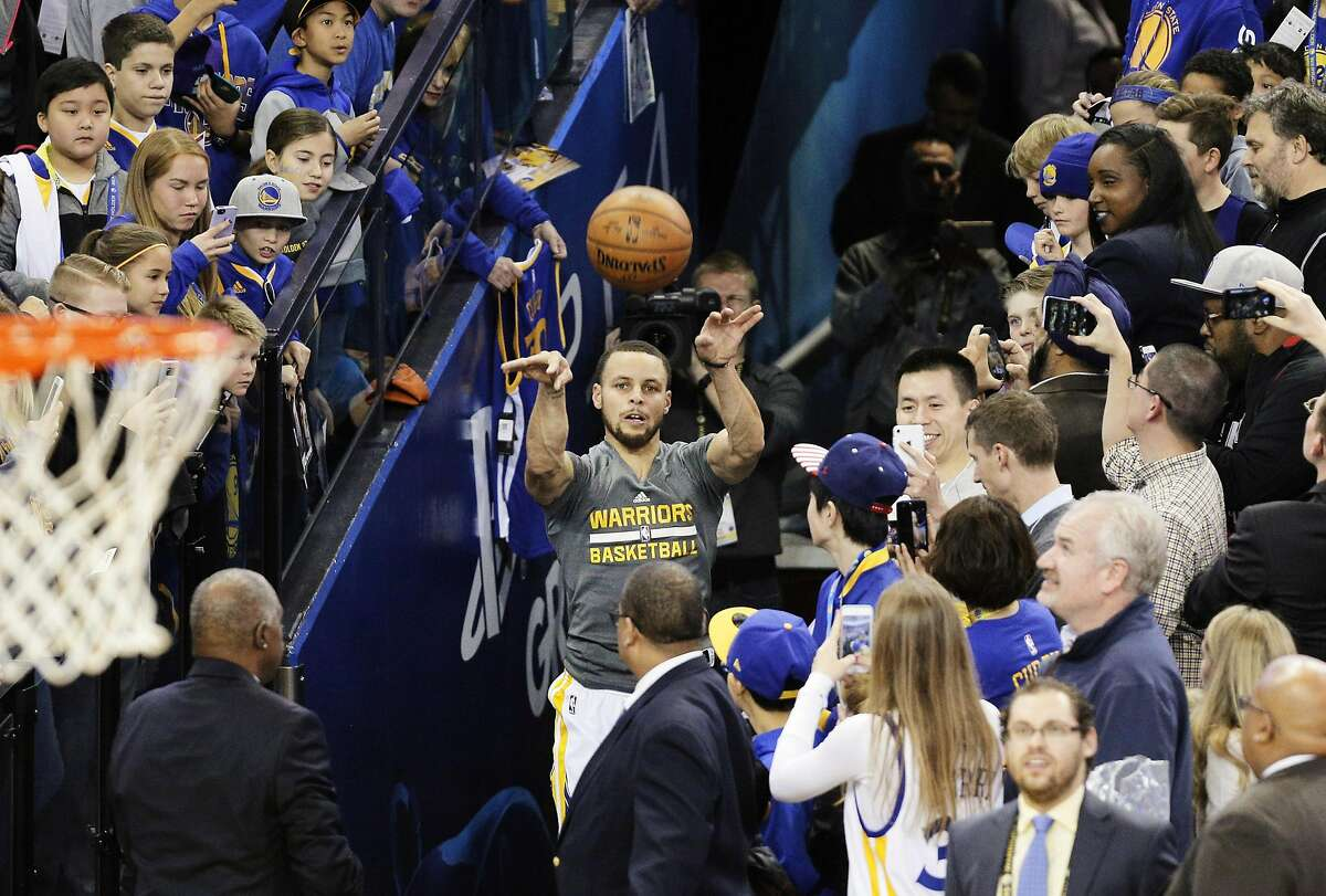 Stephen Curry (30) attempts his signature tunnel shot as fans gather by the dozens over the team entrance at Oracle Arena in Oakland, Calif., on Wednesday, February 1, 2017.