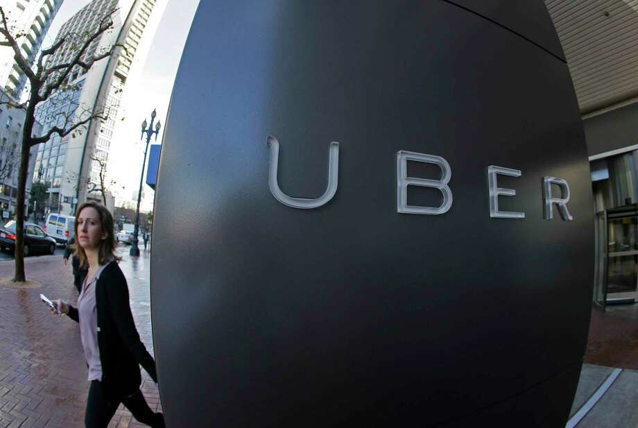 FILE - In this file photo taken Tuesday, Dec. 16, 2014, a woman walks past the company logo of the internet car service, Uber, in San Francisco, USA. Uber's chief executive ordered an urgent investigation Monday Feb. 20, 2017, into a sexual harassment claim made by a female engineer who alleged her prospects at the company evaporated after she complained about advances from her boss.  (AP Photo/Eric Risberg, FILE) Photo: Eric Risberg, STF / Copyright 2016 The Associated Press. All rights reserved.