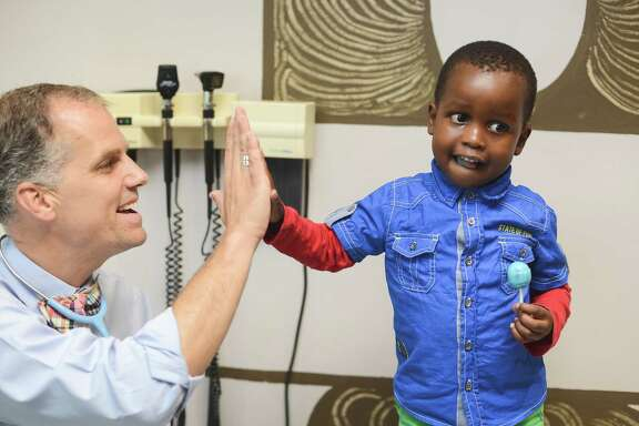 A patient high fives Dr. Alan Anderson after a check-up following treatment for kidney cancer.  Dr. Anderson is one of the pediatric oncologists from Texas ChildrenÕs Hospital who will help train the estimated 4,800 African healthcare professionals as part of the Global HOPE (Hematology-Oncology Pediatric Excellence) initiative.   Photo credit: Barcode Media