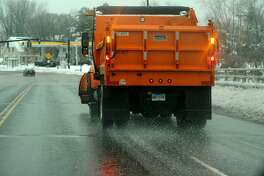 A plow truck spreads road salt on Bridgeport Avenue in Milford, Conn. on Wednesday, February 5, 2014.