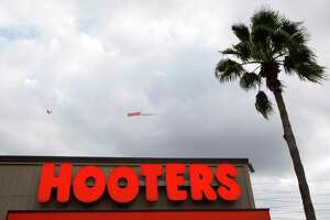 An airplane with a Hooters banner flies over the restaurant during the grand re-opening of the Hooters on Kirby Wednesday, Jan. 23, 2013, in Houston. ( Brett Coomer / Houston Chronicle )