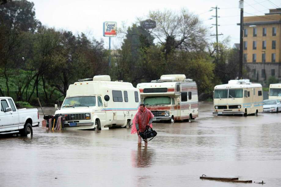 A man who lives in his RV, which was parked in the 300 block of Griffith Street in Salinas, Calif., walks through the flooded street on Mon., Feb. 20, 2016. ~ OUT: MONTEREY HERALD, SALINAS CALIFORNIAN, SANTA CRUZ SENTINEL, MONTEREY COUNTY TELEVISION NEWSMonday, Feb. 20, 2017, in Salinas, Calif. Forecasters issued flash flood warnings Monday throughout the San Francisco Bay Area and elsewhere in Northern California as downpours swelled creeks and rivers in the already soggy region. (Nic Coury/Monterey County Weekly via AP) Photo: Nic Coury, AP / Monterey County Weekly