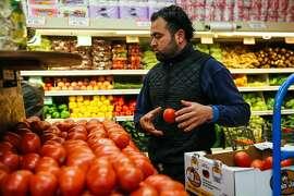 Fernando Miranda arranges tomatoes at Arteagas Food Center in San Jose, California, on Sunday, Feb. 19, 2017.