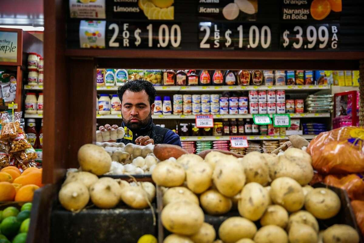 Fernando Miranda organizes the garlic at Arteagas Food Center in San Jose, California, on Sunday, Feb. 19, 2017.