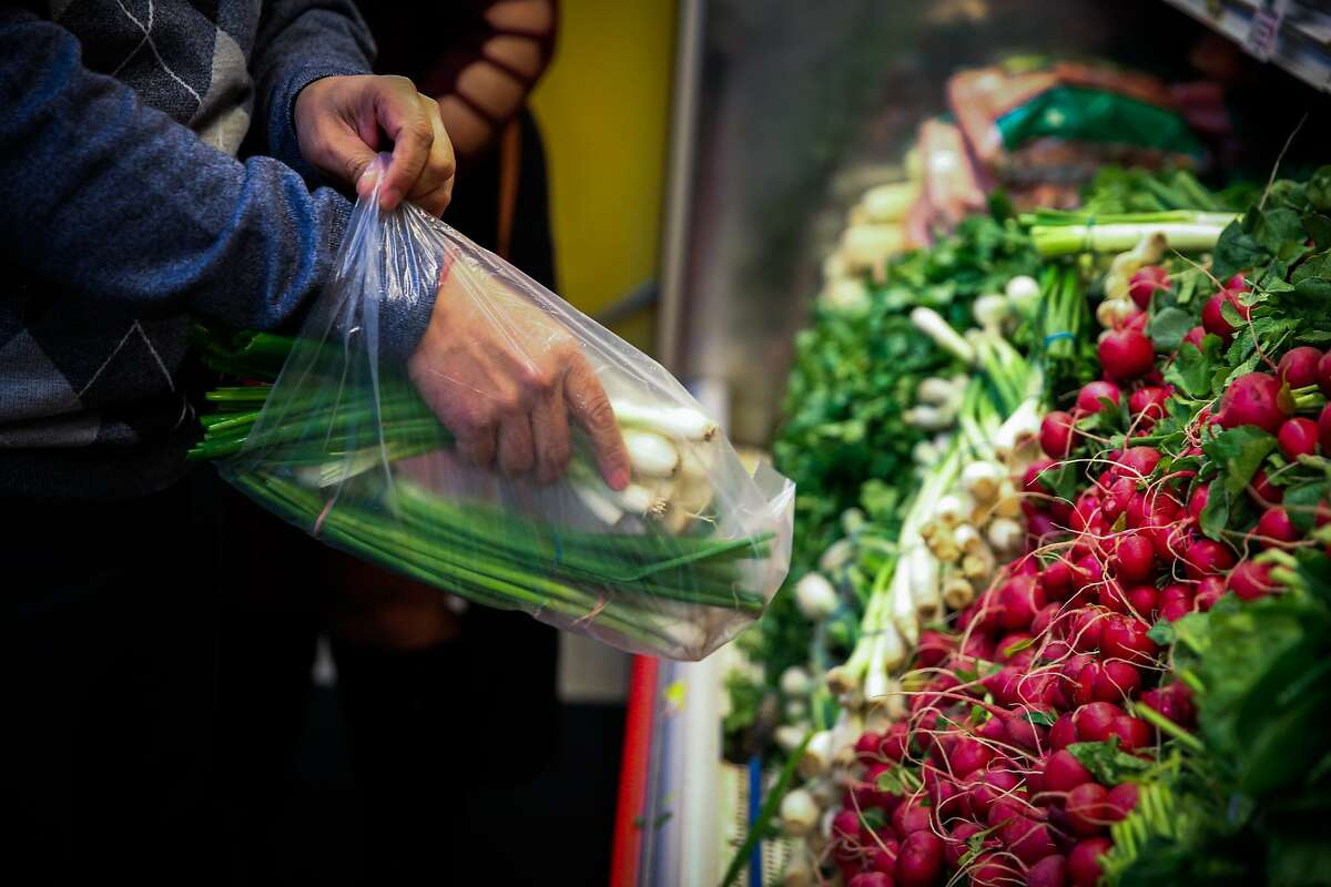 Ismael Alcala puts scallions in a plastic bag while shopping for produce at Arteagas Food Center in San Jose, California, on Sunday, Feb. 19, 2017.