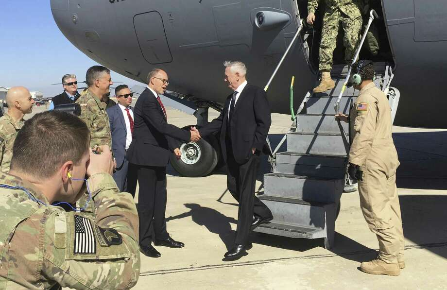 U.S. Secretary of Defense Jim Mattis, center, is greeted by U.S. Ambassador Douglas Silliman as he arrives at Baghdad International Airport on an unannounced trip Monday, Feb. 20, 2017. Mattis said Monday the United States does not intend to seize Iraqi oil, shifting away from an idea proposed by President Donald Trump that has rattled Iraq's leaders. (AP Photo/Lolita Baldor) Photo: Lolita Baldor, STF / Associated Press / Copyright 2017 The Associated Press. All rights reserved.