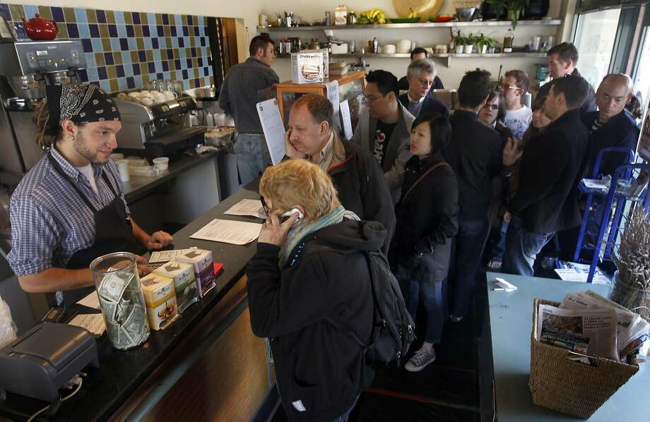 Customers wait in a long line that goes out the door to order their meals from Leo Beckerman (left) at the Wise Sons pop-up deli restaurant in San Francisco, 2011. Photo: Paul Chinn, The Chronicle