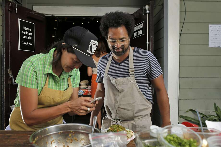 Chef Ravi Kapur, right, watches as sous chef Nana Guardia photographs a poke dish during Kapur's 2014 restaurant pop up called Paniolo Social Club. He also held pop-ups under the Liholiho Yacht Club name, prior to the restaurant opening.  Photo: Carlos Avila Gonzalez, The Chronicle