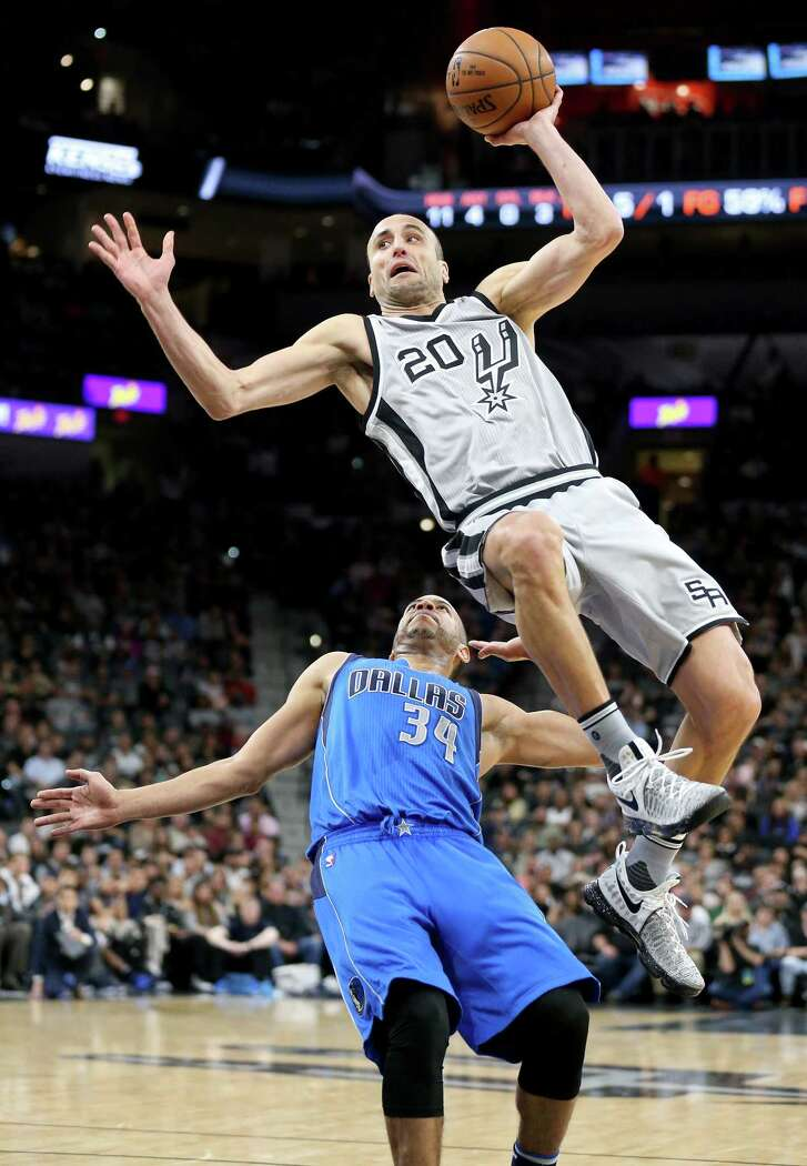 San Antonio Spurs' Manu Ginobili is fouled by Dallas Mavericks' Devin Harris during first half action Sunday Jan. 29, 2017 at the AT&T Center.