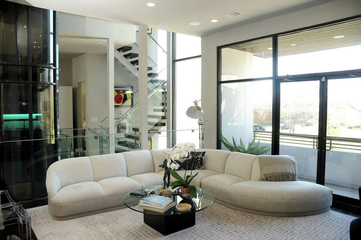 Their second-floor living room has a mix of old and new furniture. This velvety white sectional sofa was reupholstered.