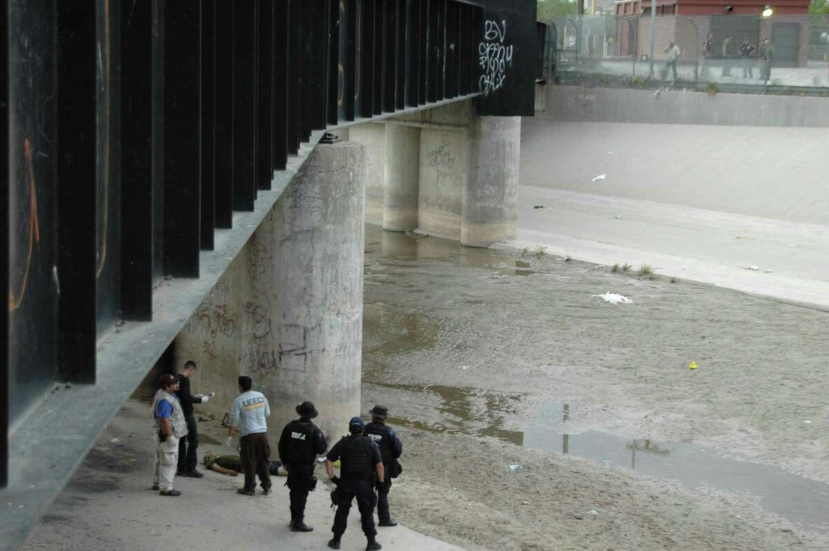 FILE - In this June 7, 2010 file photo, Mexican federal police and forensic experts stand next to the body of 14 year-old Sergio Adrian Hernandez Guereca, under the Paso Del Norte border bridge, as US officials watch from the US side at right, in Ciudad Juarez, northern Mexico. The Supreme Court appears to be evenly divided about the right of Mexican parents to use American courts to sue a U.S. Border Patrol agent who fired across the U.S.-Mexican border and killed their teenage son. (AP Photo/File)