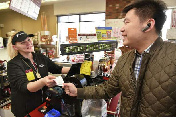 Osborne Road Stewart's Shop manager Rebecca Brown, left, sells a Powerball ticket to Xue Hui Tang of Colonie as the jackpot stands at $403 million Tuesday Feb. 21, 2017 in Colonie, NY.  (John Carl D'Annibale / Times Union)