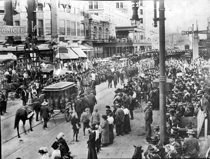 10/27/1914 - HOUSTON, TX. - GEORGE HERMANN FUNERAL PROCESSION WAS MILES LOONG AND ATTENDED BY LARGE CROWDS IN SILENT RESPECT. PHOTO LOOKS EAST WITH RICE HOTEL IN CENTER BACKGROUND, AND HOUSTON CHRONICLE ON FAR LEFT.