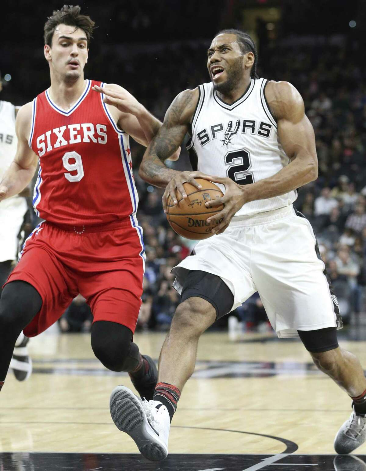 Kawhi Leonard heaves into the defense of Dario Saric as the Spurs host the Sixers at the AT&T Center on February 2, 2017.