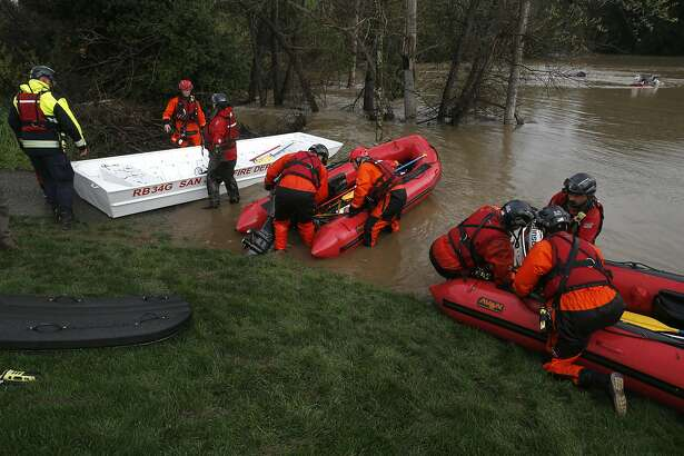 San Jose Fire swift water rescue teams collect their gear after they rescued five homeless people from the swollen Coyote Creek where were living along the banks, near the Capitol Expressway on Tuesday Feb. 21, 2017, in San Jose, Ca.