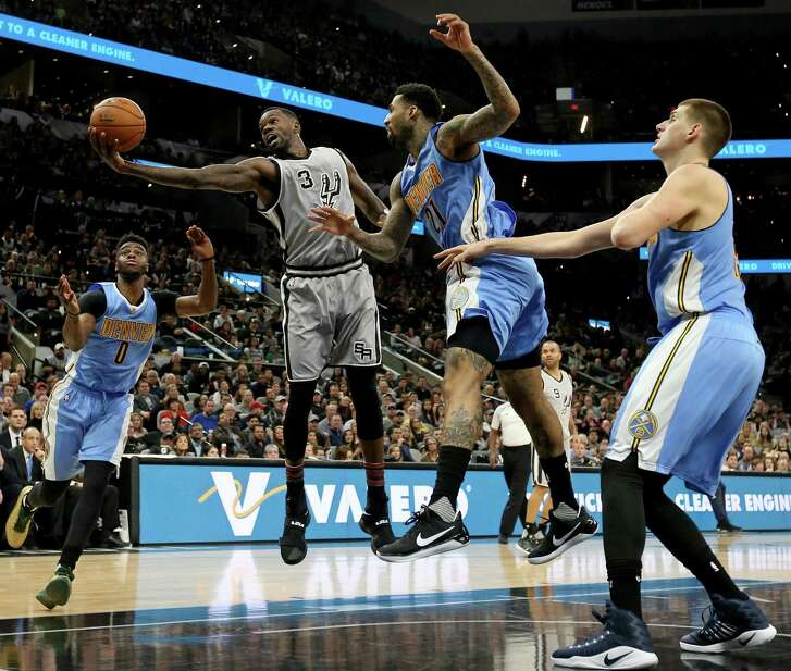 San Antonio Spurs' Dewayne Dedmon grabs for a rebound between Denver NuggetsÕ Emmanuel Mudiay (from left), Wilson Chandler, and Nikola Jokic during first half action Saturday Feb. 4, 2017 at the AT&T Center.