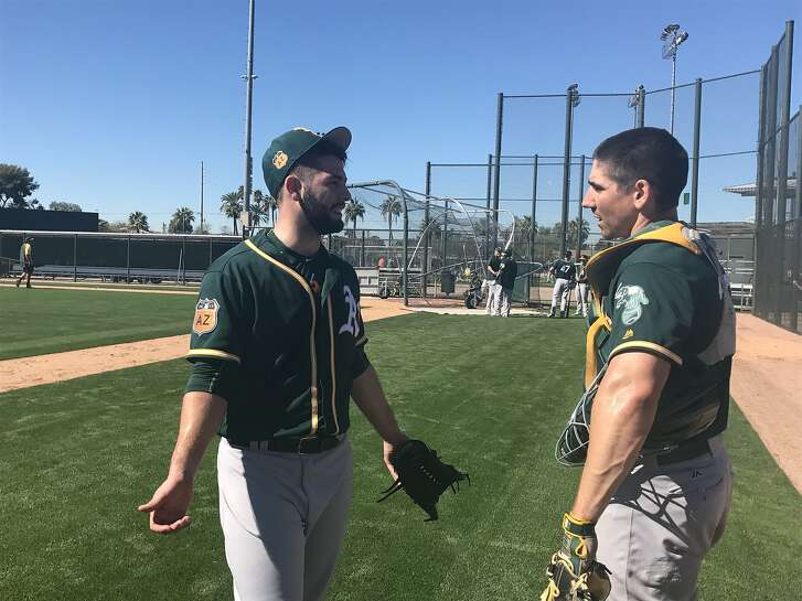 A's minor-leaguer Tucker Healy, left, talks to catcher Matt McBride after his morning throwing session Tuesday at Fitch Park in Mesa.