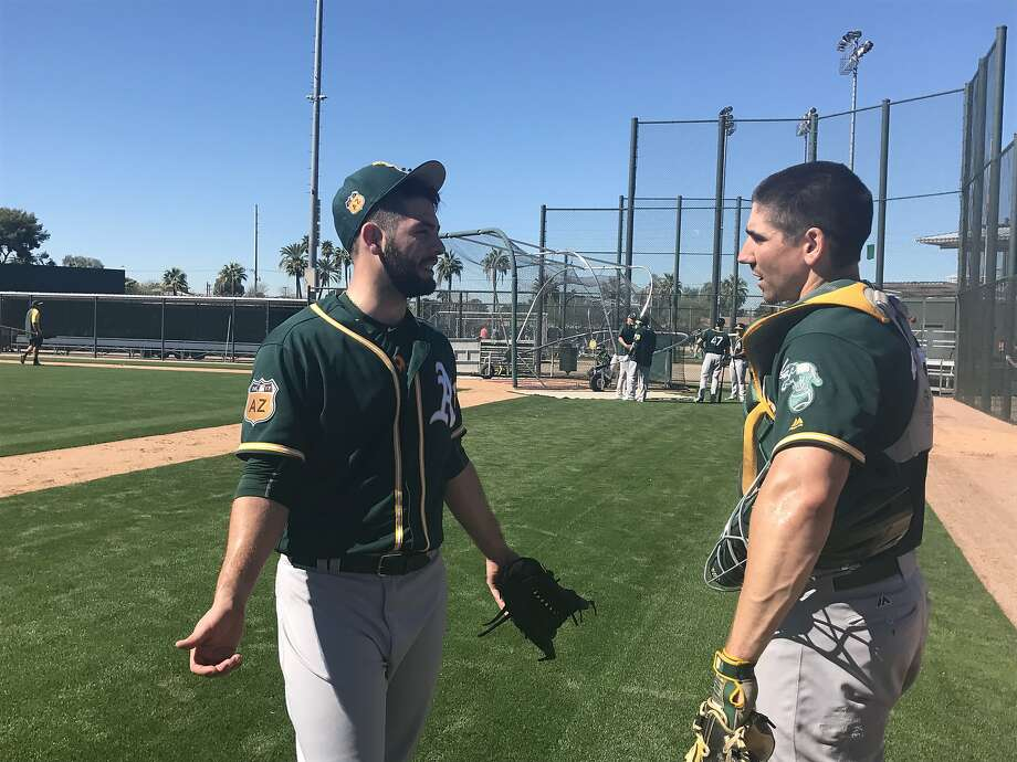 A's minor-leaguer Tucker Healy, left, talks to catcher Matt McBride after his morning throwing session Tuesday at Fitch Park in Mesa. Photo: Susan Slusser, The Chronicle