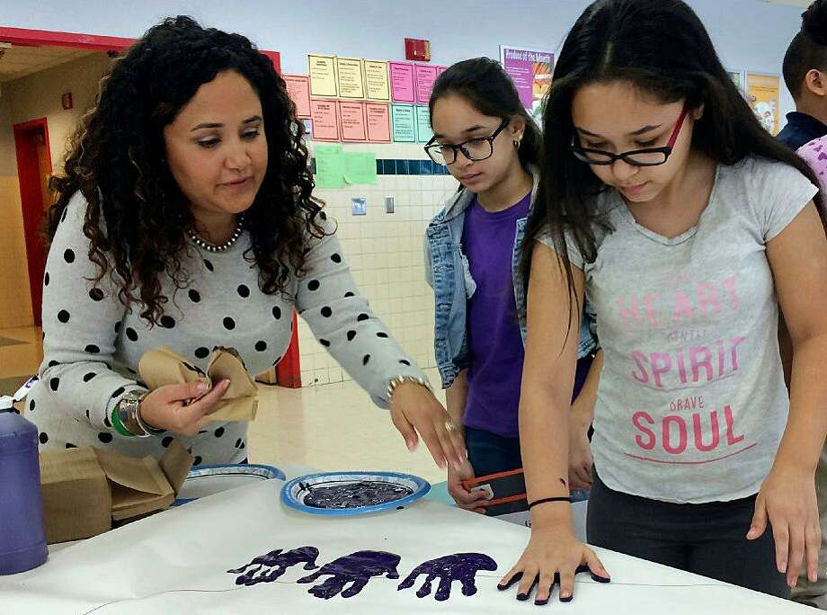 Nelba Marquez-Greene helps 10-year-old Araceli Buchko put her hand print inside a giant paper heart as part of the Love Win's campaign's Friendship Day, a social and emotional learning activity at the Chamberlain Elementary School in New Britain. Photo: / AP Photo / Pat Eaton-Robb)