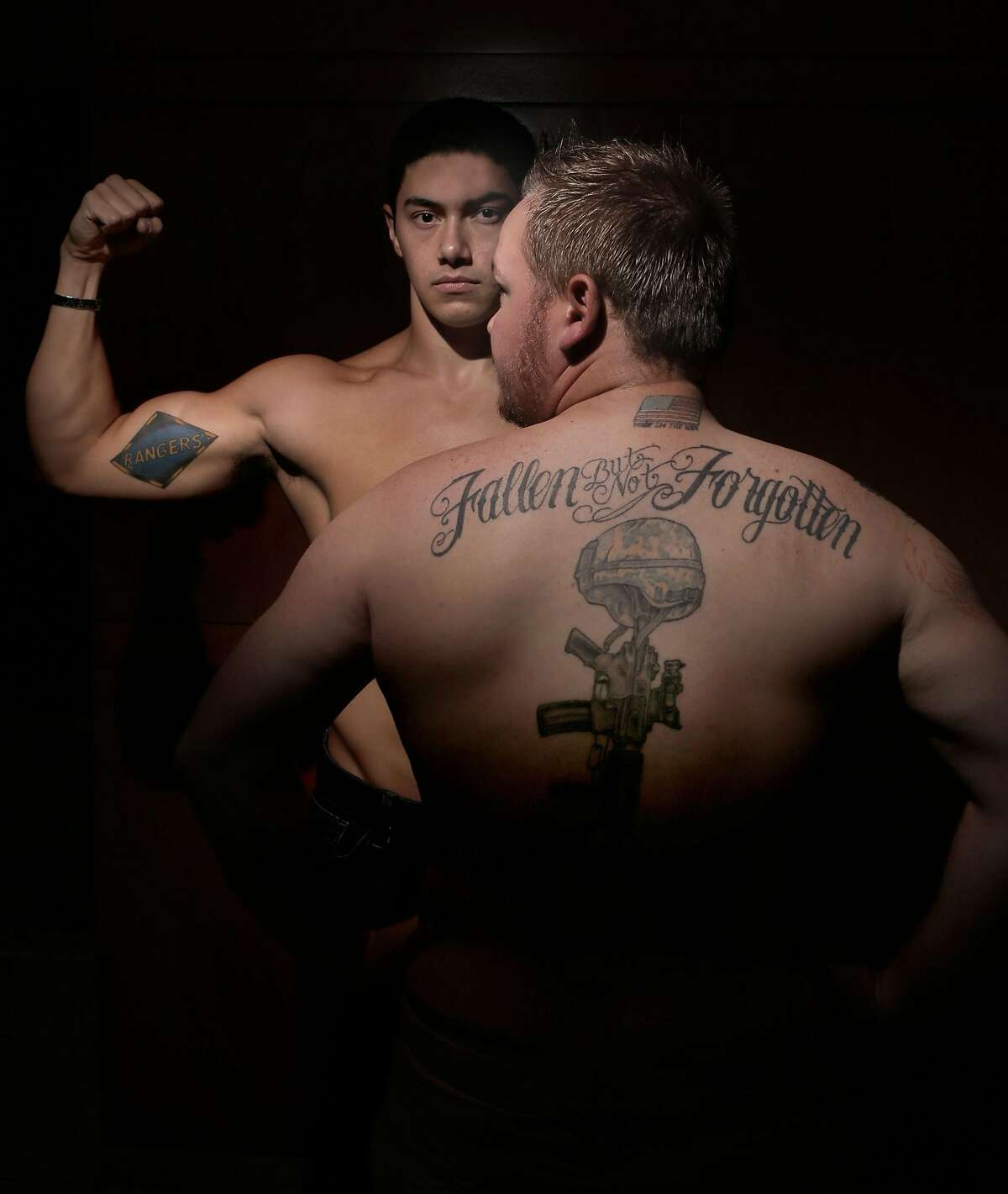 William Glazier, (left) of Gilroy, who served with the 1st Ranger Battalion of the US Army and Jonathan Snyder, of Des Moine, Iowa, who served with the US Army 4th Engineer Battalion display their tattoos, as seen on Friday Nov. 7, 2014 in Oakland, Calif. Veterans of the Iraq and Afghanistan wars come together to display their tattoos for an exhibition called War Ink.