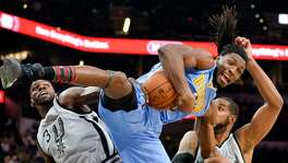 Denver Nuggets forward Kenneth Faried, center, falls as he jumps for a rebound against San Antonio's Dewayne Dedmon, left, and LaMarcus Aldridge on Feb. 4, 2017, in San Antonio.