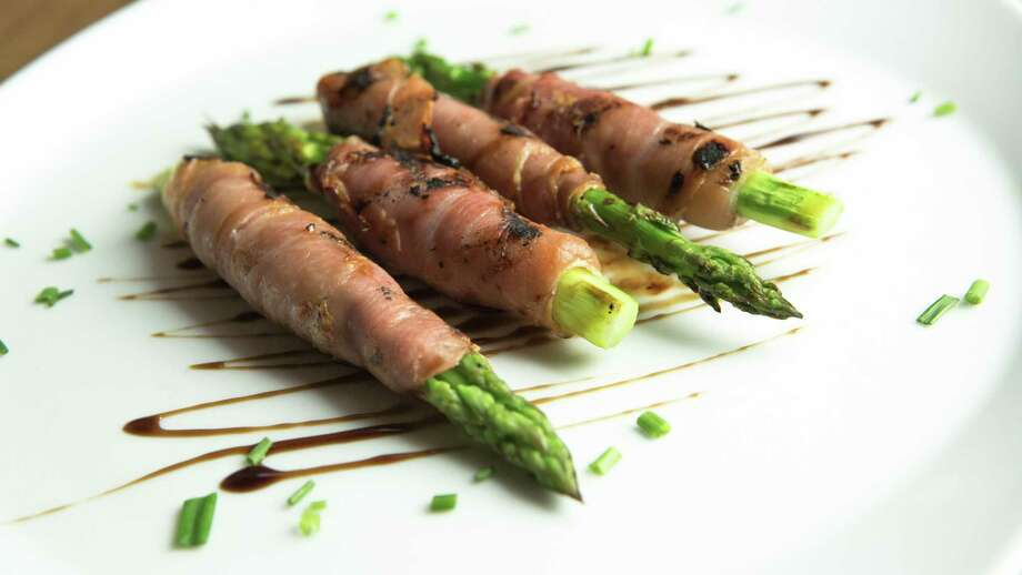 Looking for an elegant, but simple way, to celebrate Oscar night? Chef Rolando Guardado, of Cotto restaurant in Stamford, suggests wrapping an asparagus spear with prosciutto and drizzling it with balsamic glaze. Photo: MaxEx PR / Contributed Photo / Connecticut Post contributed