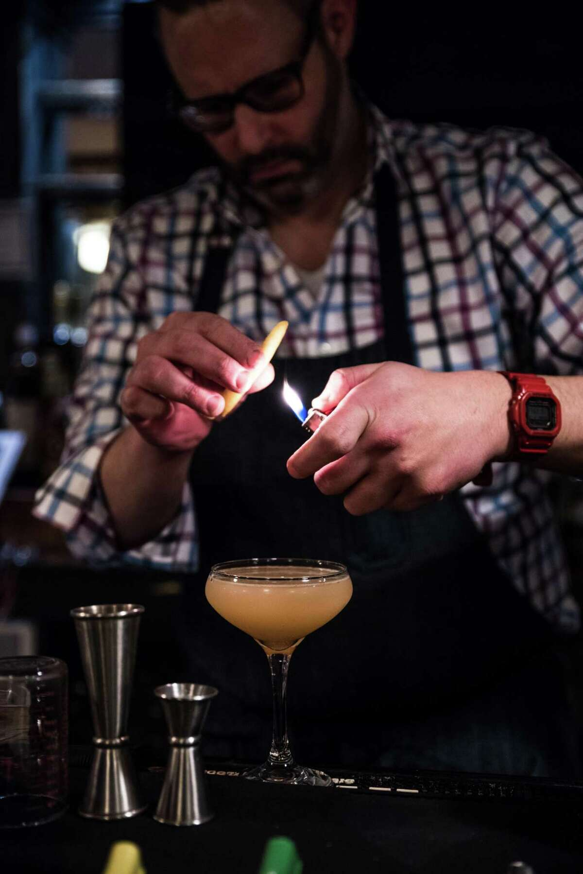Tom Siano, bar manager at Peaches in Norwalk, takes a lighter to a garnish on a cocktail he created for an Oscar-themed viewing party.