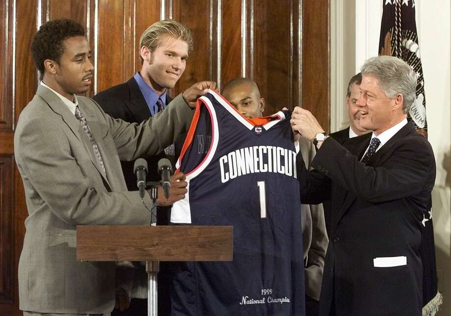 President Clinton receives a commemorative jersey presented by University of Connecticut basketball players from left Kevin Freeman, Jake Voskuhl, Ricky Moore and UCONN Coach Jim Calhoun during a ceremony honoring the team at the White House Thursday, Oct. 14, 1999. UCONN beat a heavily favored Duke team to win the NCAA National Championship last spring. (AP Photo/Greg Gibson) Photo: GREG GIBSON/ASSOCIATED PRESS