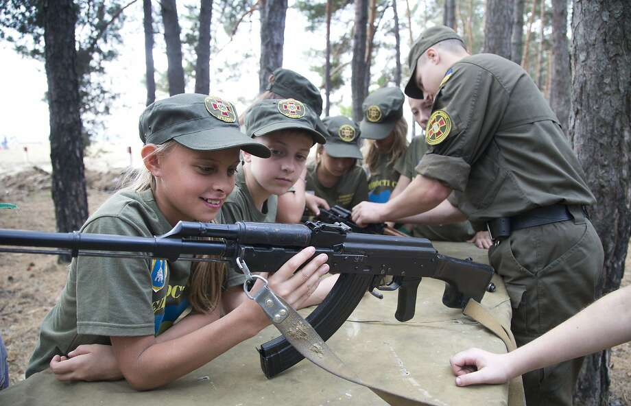 A serviceman teaches children to operate weapons at a Ukraine National Guard training camp in 2015. Photo: Efrem Lukatsky, Associated Press