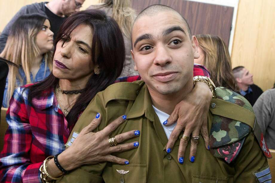 Sgt. Elor Azaria, is embraced by his mother, Oshra, at the start of his sentencing hearing in a military court in Tel Aviv for the slaying of a Palestinian man who attacked a fellow soldier. Photo: JIM HOLLANDER, AFP/Getty Images