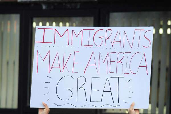 "Gabby Perez, 17, of Danbury, holds a ""Immigrants make America great"" sign at a ""Day without immigrants"" rally at the Danbury City Hall Thursday, February 16, 2017."
