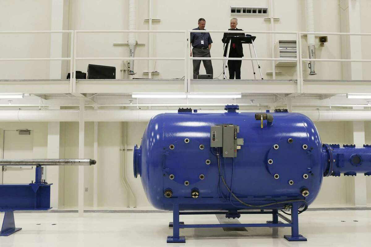 Hermam Monroe (left) and James Walker, director of mechanical and material engineering, look over the new high-velocity gas gun that will be used for impact studies at the Southwest Research Institute.