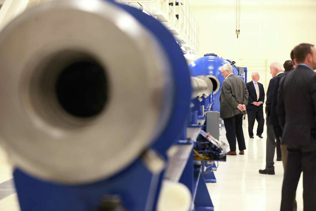 Members of the Southwest Research Institute advisory trustees and board of directors are shown a two-stage light gas gun in 2017. The institute jumped on the hunt for a COVID-19 treatment as soon as the virus' protein was published in February.