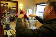 Wayne DeVingo finishes up with Cathy Malloy, wife of Connecticut Gov. Dannel P. Malloy and a client of Wayne Salon in Stamford, Conn. on Feb. 18, 2017. The salon recently relocated to a space in the My Salon Suite complex on High Ridge Road.