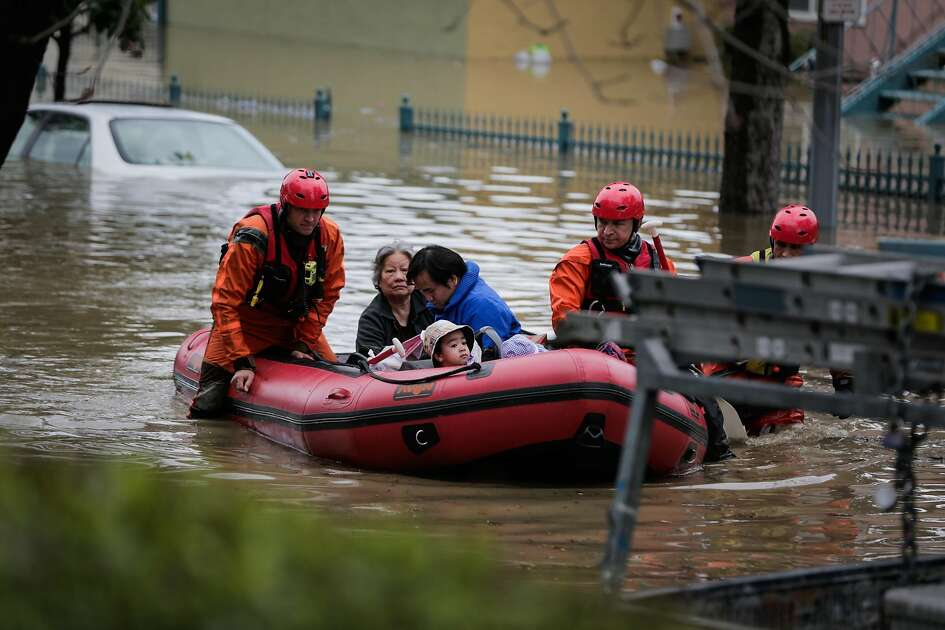 People are seen on a boat as they evacuate from their homes following severe flooding on Nordale Street in San Jose, California, on Tuesday, Feb. 21, 2017.