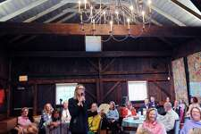 Bonnie Levenson, a Greenwich Historical Society board member, speaks during Story Barn, a Greenwich Historical Society event giving Greenwich residents the opportunity to tell five-minute stories based on personal experiences connected with Greenwich, at the society in Cos Cob.