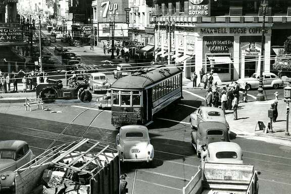 """From the back of the photo: """"F Car goes through - The two months long blockade of the Fourth and Market intersection ended completely yesterday morning as F cars moved from Fourth Street across Market into Stockton. While police officers experimented with the new traffic pattern at the complex five-way intersection, workmen rolled down the last of the  fill in the project. City officials hope the revised schedule will end one or more downtown bottlenecks."""" September 9, 1947."""