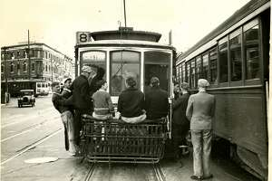 Passengers sitting on a streetcar cow-catcher at Church, 14th and Market Streets in San Francisco, ca 1930's.