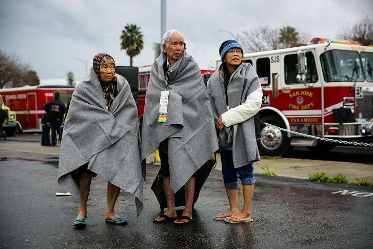 Quang Tang (left) and her husband Gong Tang and daughter Danz Tang (right) were evacuated by boat from their home due to severe flooding in San Jose, California, on Tuesday, Feb. 21, 2017.