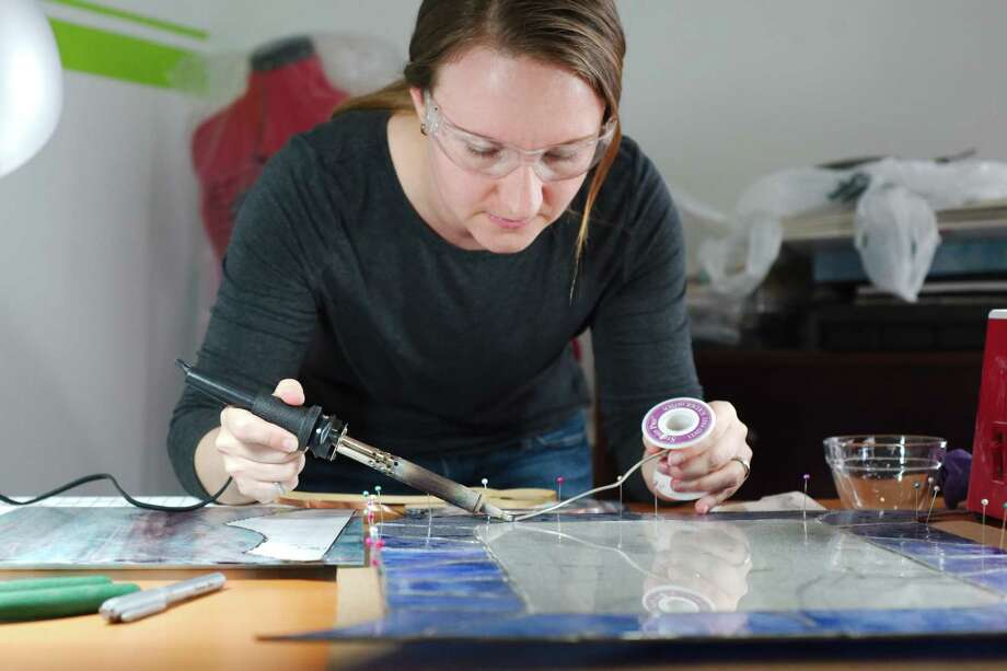 "NASA robotics engineer and stained-glass artist Laura Lucier solders a piece of  glass as she works on a project in her Clear Lake home studio. ""Art and science go hand in hand nicely. Either way, you're solving a problem creatively,"" she says. ""You're having to think outside the box for ways to get a goal accomplished."" Photo: Kirk Sides / © 2016 Kirk Sides / Houston Community Newspapers"