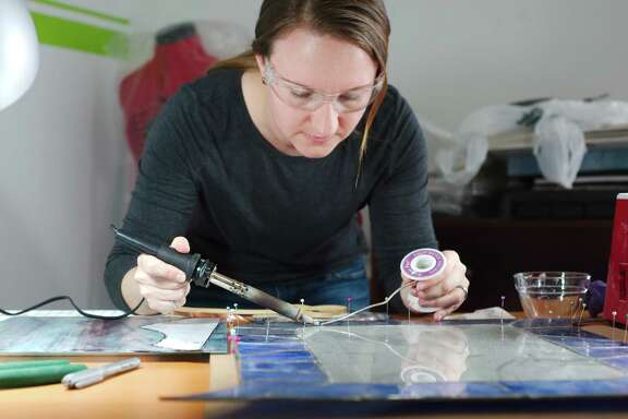 """NASA robotics engineer and stained-glass artist Laura Lucier solders a piece of  glass as she works on a project in her Clear Lake home studio. """"Art and science go hand in hand nicely. Either way, you're solving a problem creatively,"""" she says. """"You're having to think outside the box for ways to get a goal accomplished."""""""