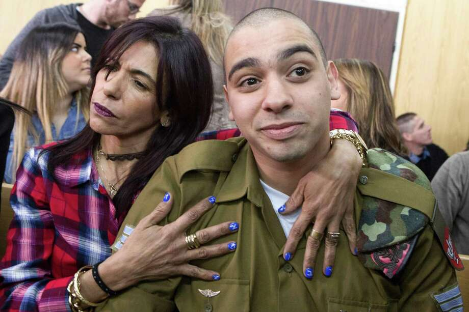 Israeli soldier Elor Azaria, embraced by his mother Oshra on Tuesday at his sentencing, was convicted of manslaughter last month but has received widespread community support.  Photo: JIM HOLLANDER, Stringer / AFP