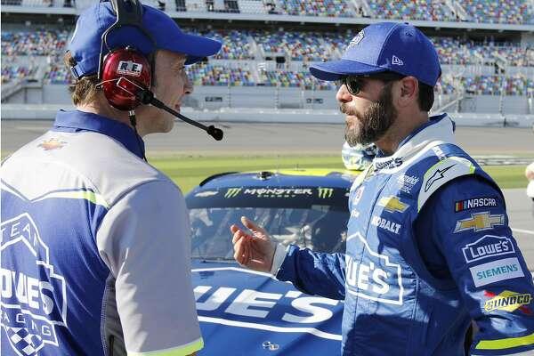 Jimmie Johnson, right, talks with crew chief  Chad Knaus on pit road after a qualifying run for the NASCAR Daytona 500 auto race at Daytona International Speedway, Sunday, Feb. 19, 2017, in Daytona Beach, Fla. (AP Photo/Terry Renna)