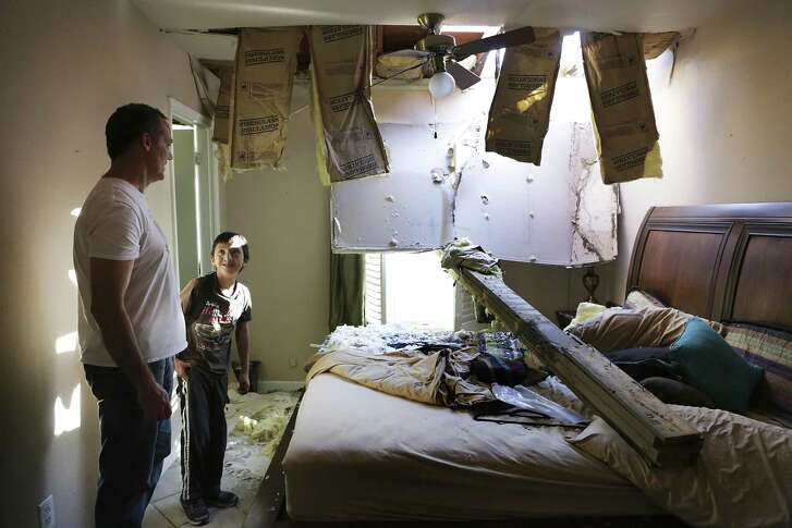 Ed McCormick, left, and his son Xander, 11, observe the bed that McCormick was sleeping in when he was awakened by the tornado warning alarm on his phone on Sunday night.  He got up to check on his wife and children in the next room, when only twenty seconds later the bean came crashing through the window and came to rest where he had been sleeping. Residents in the Alamo Heights School District look at the damage done to their property by the tornadoes that hit San Antonio last Sunday.