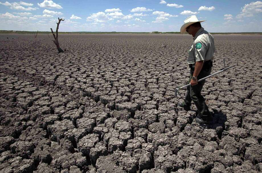 Texas State Park police officer Thomas Bigham walks across the cracked lake bed of O.C. Fisher Lake in San Angelo in 2011. Trump inaction on climate change today will leave a legacy of destruction for millenials and those who come after will pay for. Photo: Tony Gutierrez /Associated Press / AP