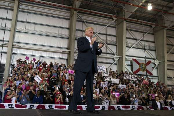 President Donald Trump arrives at a rally at Orlando Melbourne International Airport, in Melbourne, Fla., on Saturday. He continued portraying journalists as the enemy of the people.